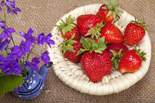 Bouquet of flowers in a ceramic teapot and strawberries in a wic