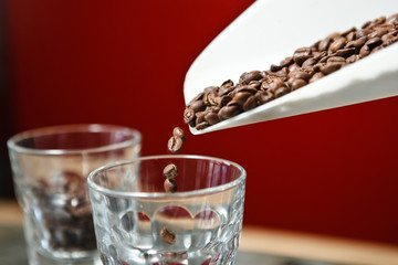 Roasted coffee beans pouring in glass