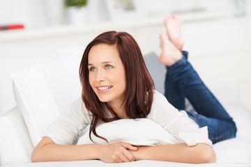 lächelnde frau liegt entspannt auf dem sofa