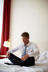 junger Mann mit Tablet-PC auf Hotelzimmer