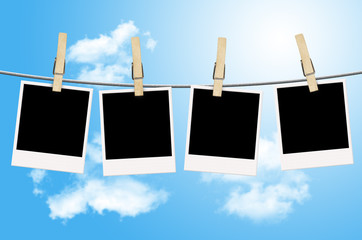 Blank photographs hanging on a clothesline with blue sky