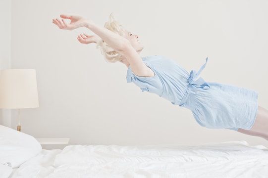 Junge Frau springt ins Bett