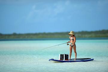 Printed kitchen splashbacks Fishing Woman in bikini fishing and paddle boarding