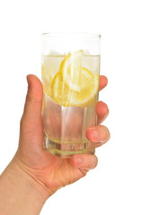 Man's hand holding glass of water with ice and lemon