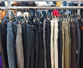 different group colored jeans hanging on a hanger in store shop