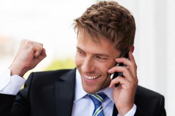 erfreuter Geschäftsmann beim telefonieren