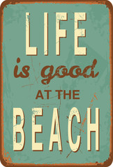 """Vintage style tin sign with text """"Life is good at the Beach""""."""