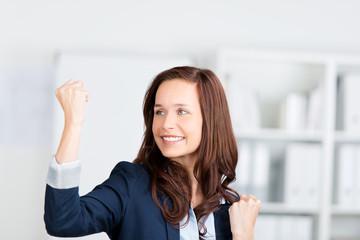 glückliche frau im büro ballt die faust