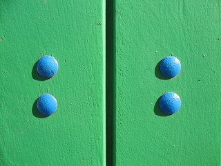 A fragment of a wooden door with bolts