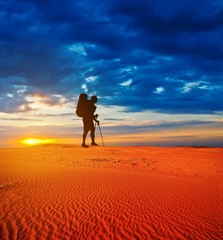 tourist in a sand desert at the sunset