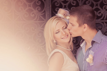 Wedding kissing pair against gate