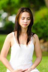 Beautiful healthy Young Woman meditating on the green grass