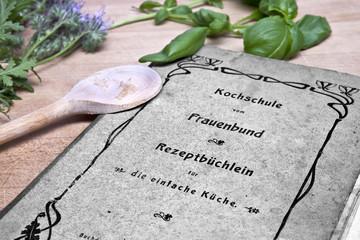 Das alte Kochbuch von Oma mit Kochlöffel und Basilikum