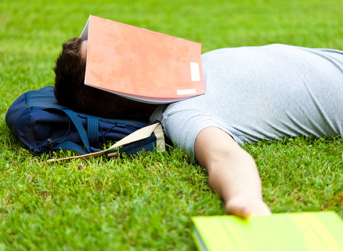 Tired student sleeping with a book over is face at the park