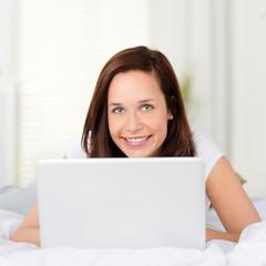 lächelnde frau schaut über laptop
