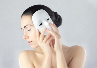 Obraz Młoda kobieta trzymająca maskę obok twarzy - fototapety do salonu