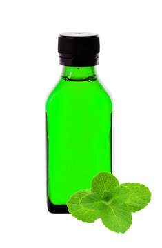 Close up of medicine bottle with green syrup and mint herb isola