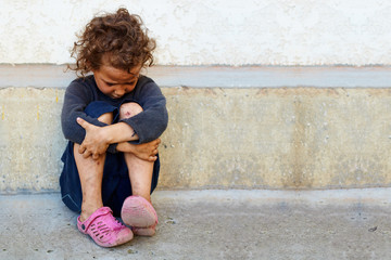 poor, sad little child girl sitting against the concrete wall