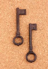 Two antique keys on cork background