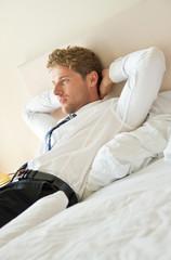 entspannter Mann liegt auf Bett