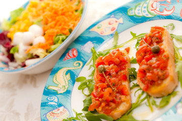 Mix Salad with tomato bruschetta on background.