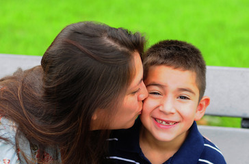 Mom kissing young son on cheek