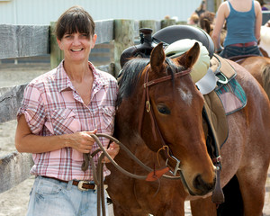 A smiling woman takes a break during a horse event.