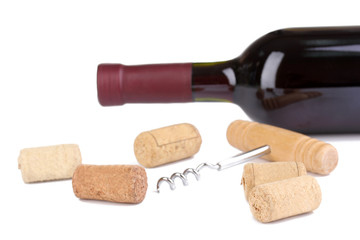 Bottle of wine with corkscrew and wine corks isolated on white