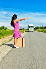 Woman with suitcase hitchhiking a car