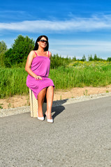 Woman sitting on suitcase on the road.