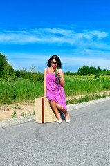 Woman with rose sitting on suitcase on the road