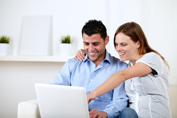 Young couple smiling and pointing to laptop screen