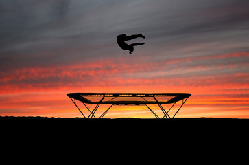 Wall Mural - silhouette of gymnast on trampoline in sunset