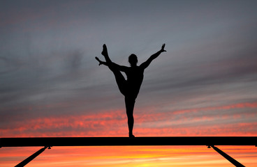 Wall Mural - silhouette of female gymnast on balance beam in sunset