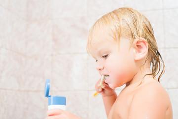 Adorable baby brushing teeth staying in bath