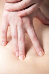 Closeup photo of masseur's hands doing deep tissue massage