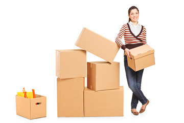 Smiling woman holding a box and many other boxes around her