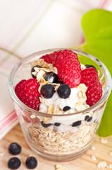 Muesli with yogurt raspberries and blueberries for breakfast