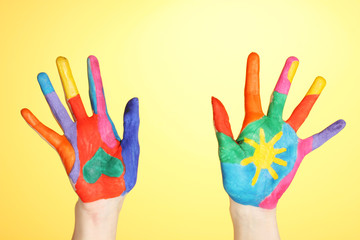 Brightly colored hands on yellow background close-up