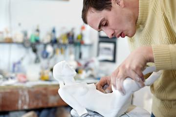 Sculptor carefully attach legs to  plaster statuette