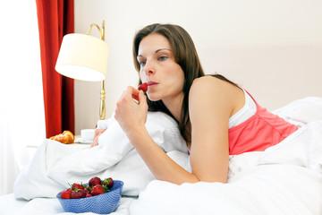 Frau frühstückt im Bett