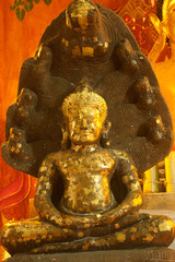 Ancient sitting Buddha in old temple in Thailand.