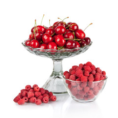 fresh raspberries and red cherries in a bowl isolated on white