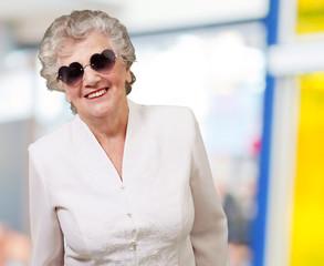 portrait of happy senior woman wearing heart glasses indoor