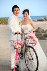 groom and bride standing beside old bicycle