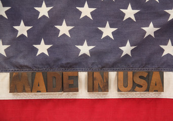 the words made in USA in old wood type on an American flag