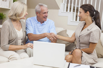 Saleswoman Shaking Hands With Senior Couple at Home