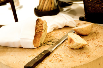 Wooden cutting board with sliced white bread and knife on wooden