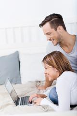 paar mit laptop im bett