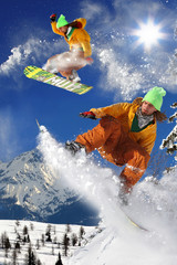 Wall Mural - Snowboarders jumping against blue sky
